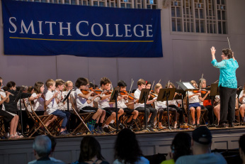 Student orchestra performs on stage facing the conductor in a bright blue blouse, while an audience in the foreground looks on.