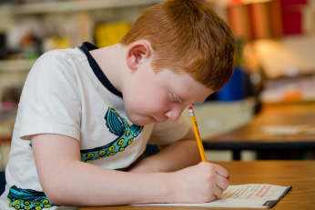 A boy in a t-shirt with a pencil in his hand and a determined expression is hunched over a paper.