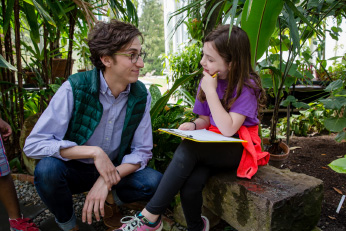 In the arboretum, a young man squats in front of a young girl sitting on a bench with a clipboard in her lap. The girl has her chin resting on her hand and appears to be thinking about something that she and the man are discussing,