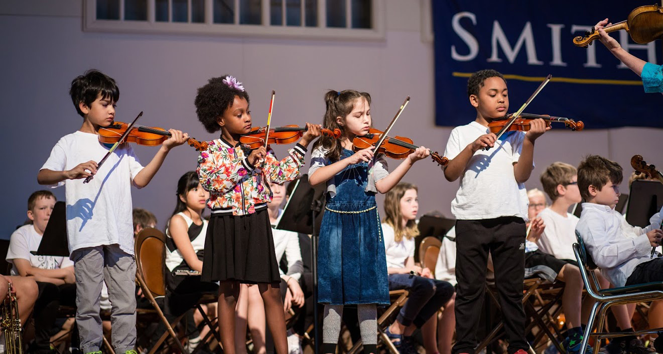 Students on stage playing violin