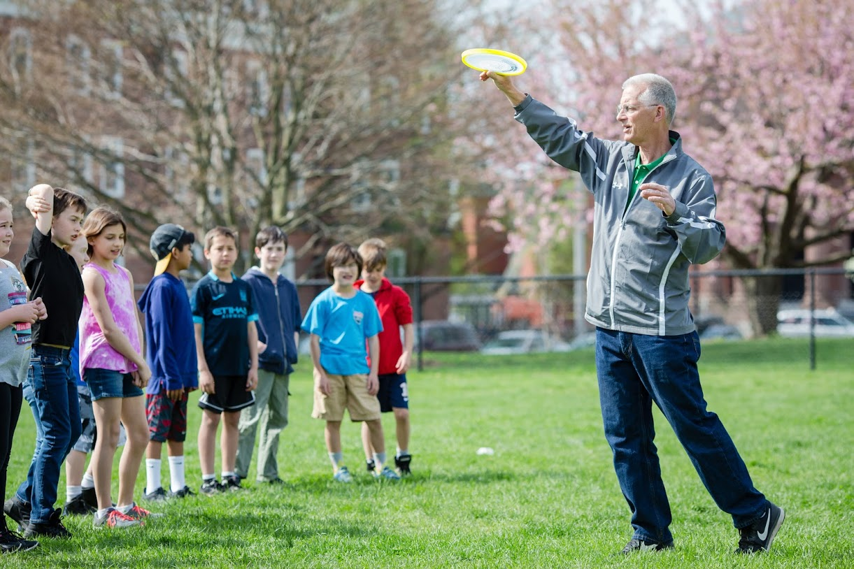 students learning how to throw frisbees