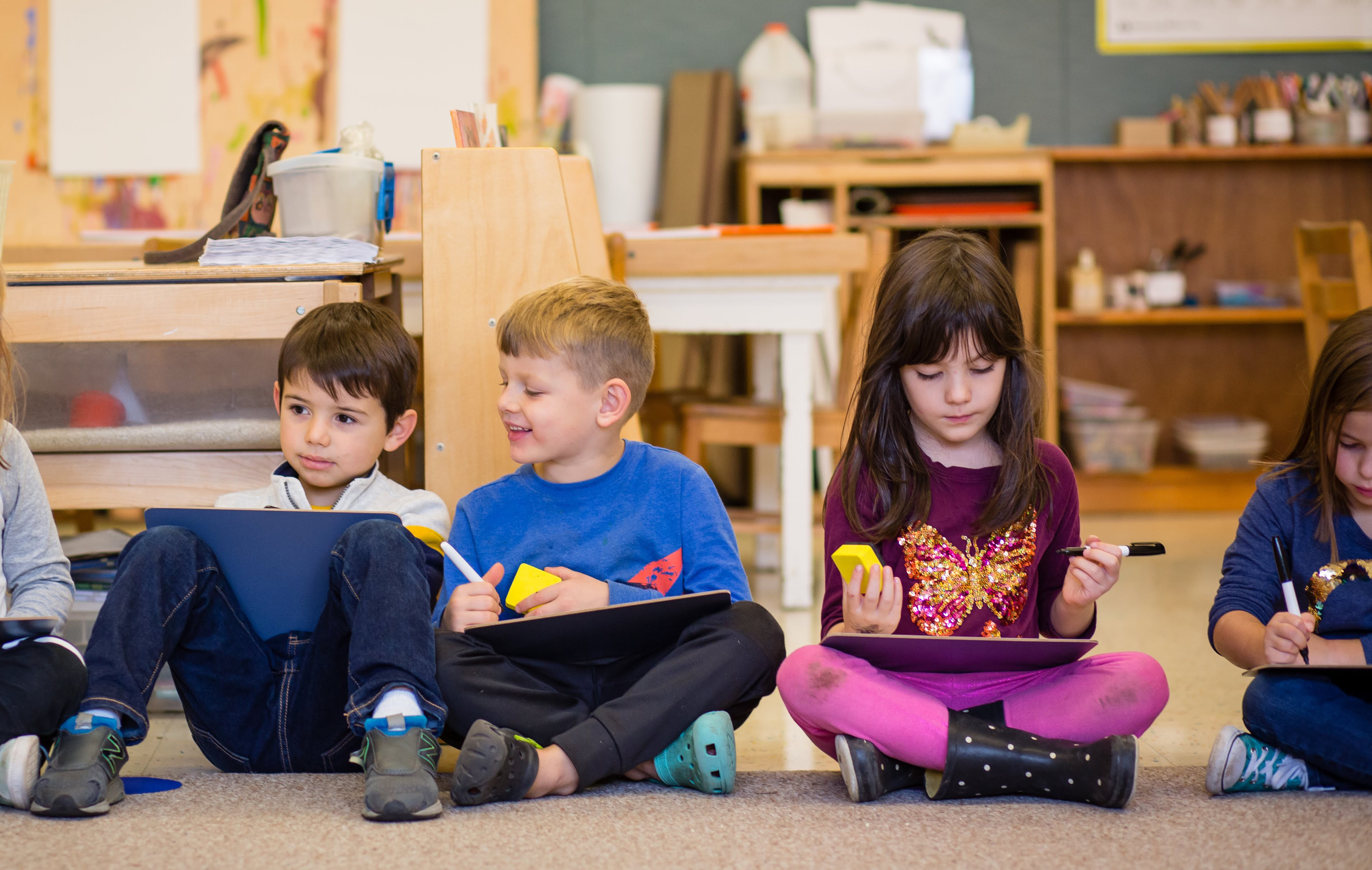 two kindergarten boys and two kindergarten girls sitting on the rug practicing handwriting